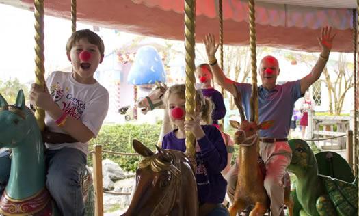 Harris Rosen riding carousel with kids