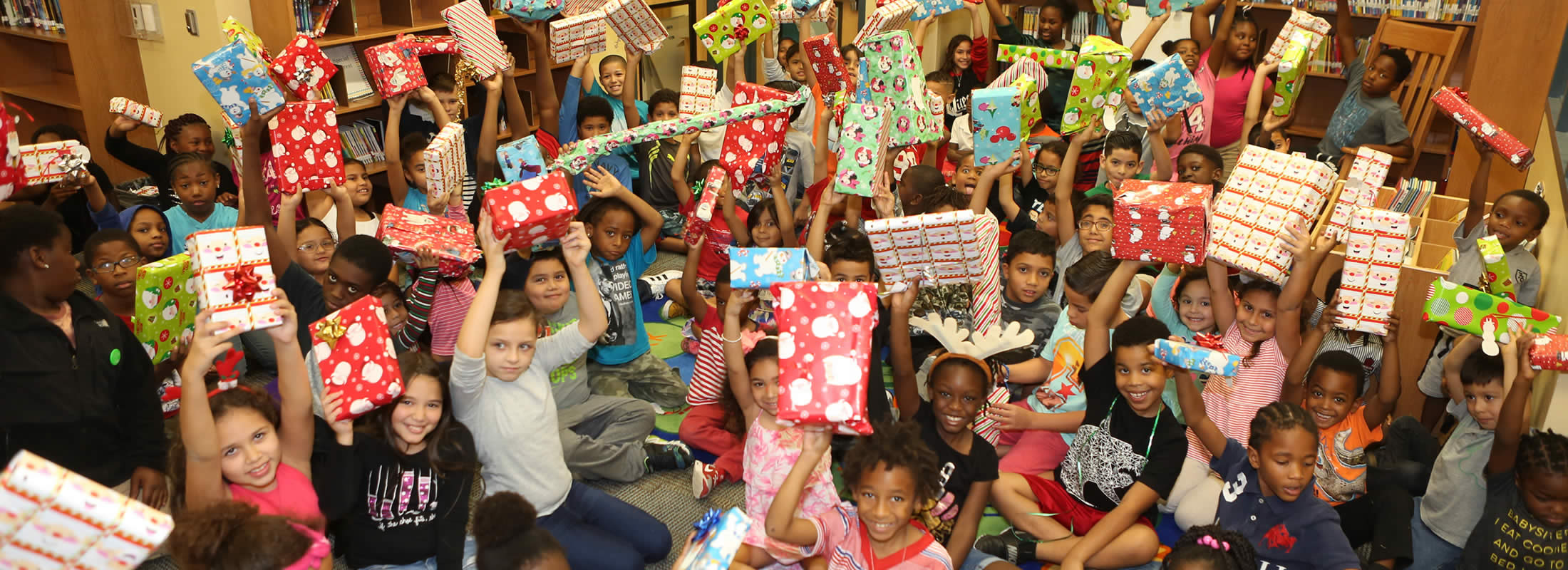 Children holding up Christmas presents, part of the Tangelo Park Program